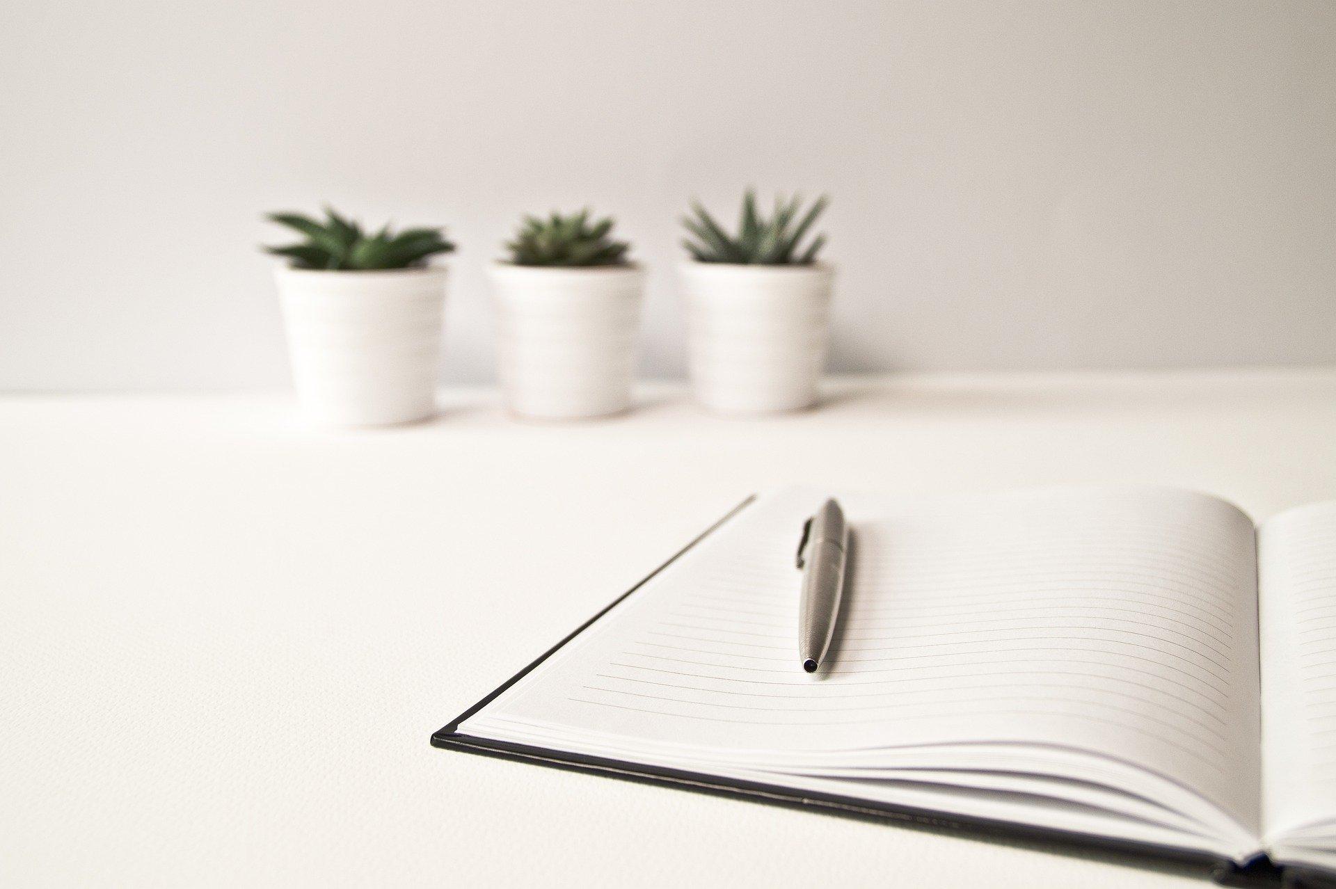 Foto von aufgeschlagenem Notizbuch mit Stift